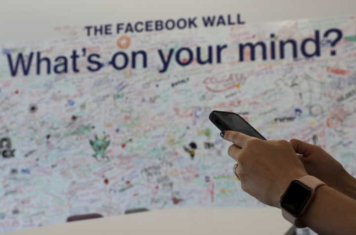 In this Monday, May 20, 2019 photo, a woman uses her mobile at the Facebook office in Dubai, United Arab Emirates. The Muslim holy month of Ramadan, with its long days of fasting and prayer meant to draw worshippers closer to God and away from worldly distractions, is being reshaped by technology. People in the Middle East are spending close to 58 million more hours on Facebook and watching more YouTube videos than at any other time of the year, making Ramadan the biggest moment of the year for advertisers. (AP Photo/Kamran Jebreili)