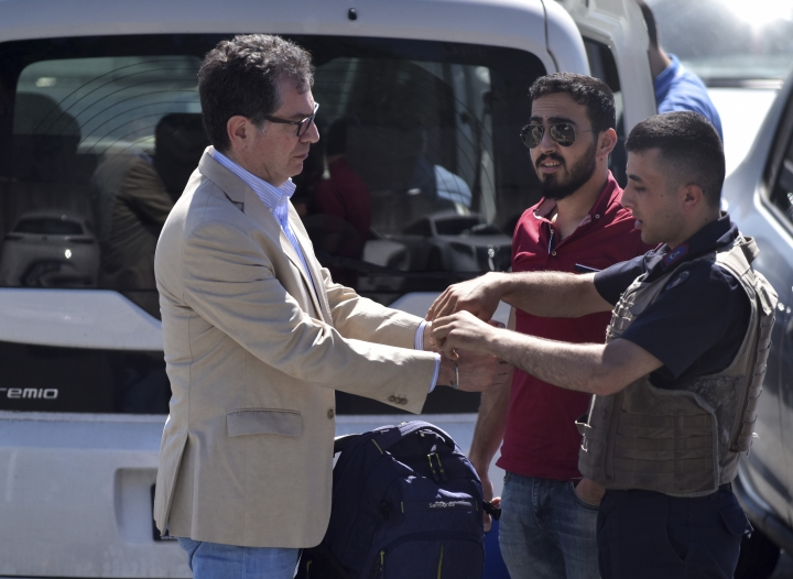 Kadri Gursel, left, a prominent Turkish journalist, is handcuffed by police as he turns himself in outside an Istanbul prison, Wednesday, May 29, 2019. Gursel, sent back to prison Wednesday in connection with convictions for terror charges handed last year to an opposition newspaper, was released hours later. (DHA via AP)