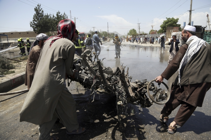 Afghan people carry the remains of suicide attacker's vehicle in Kabul, Afghanistan, Friday, May 31, 2019. In a second suicide attack in as many days to rattle the Afghan capital, a car bomb targeting a U.S. convoy exploded early Friday morning in an eastern neighborhood, police said. (AP Photo/Rahmat Gul)