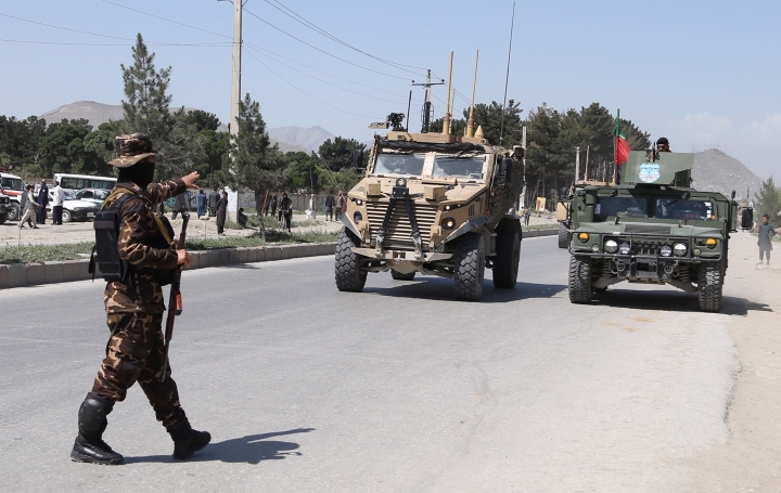 A soldier directs NATO forces arriving at the site of a suicide attack in Kabul, Afghanistan, Friday, May 31, 2019. A suicide car bomb exploded early Friday morning in an eastern neighborhood of the capital Kabul, leaving seven casualties, police said. (AP Photo/Rahmat Gul)