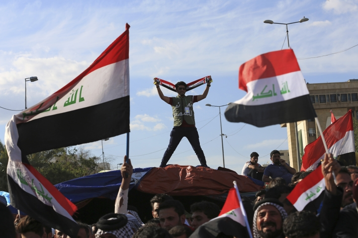 FILE - In this March 31, 2016 file photo, followers of Shiite cleric Muqtada al-Sadr wave national flags as they end their sit-in outside the heavily guarded Green Zone in Baghdad, Iraq. The zone has been a barometer for tension and conflict in Iraq for nearly two decades. The sealed-off area, with its palm trees and monuments, is home to the gigantic U.S. Embassy in Iraq, one of the largest diplomatic missions in the world. It has also been home to successive Iraqi governments and is off limits to most Iraqis. (AP Photo/Khalid Mohammed, File)