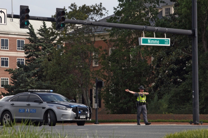 A police officer directs traffic away from the intersection of Princess Anne Road and Nimmo Parkway following a shooting at the Virginia Beach Municipal Center on Friday, May 31, 2019, in Virginia Beach, Va. At least one shooter wounded multiple people at a municipal center in Virginia Beach on Friday, according to police, who said a suspect has been taken into custody. (Kaitlin McKeown/The Virginian-Pilot via AP)