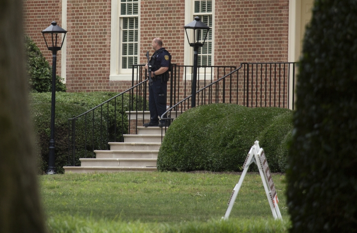 A police officer stands out in front of City Hall next to the building where eleven people were killed during a mass shooting at the Virginia Beach city public works building, Friday, May 31, 2019 in Virginia Beach, Va. A longtime, disgruntled city employee opened fire at a municipal building in Virginia Beach on Friday, killing 11 people before police fatally shot him, authorities said. Six other people were wounded in the shooting, including a police officer whose bulletproof vest saved his life, said Virginia Beach Police Chief James Cervera. (L. Todd Spencer/The Virginian-Pilot via AP)