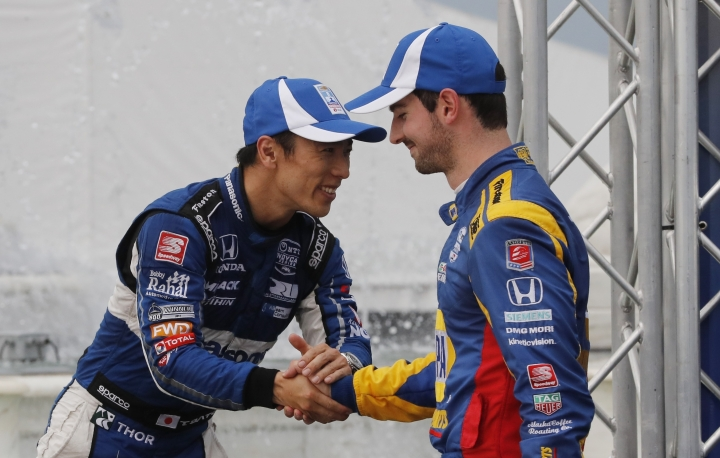 Second-place finisher Alexander Rossi, right, shakes hands with third-place finisher Takuma Sato of Japan, after the first race of the IndyCar Detroit Grand Prix auto racing doubleheader, Saturday, June 1, 2019, in Detroit. (AP Photo/Carlos Osorio)