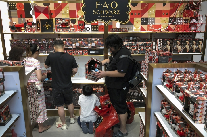 """In this Saturday, June 1, 2019, photo, Chinese shop for toys at the newly opened FAO Schwarz toy store at the capital city's popular shopping mall in Beijing. China issued a report Sunday blaming the United States for a trade dispute and says it won't back down on """"major issues of principle."""" (AP Photo/Andy Wong)"""