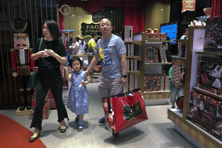 """In this Saturday, June 1, 2019, photo, Chinese buy toys at the newly open FAO Schwarz toy store at the capital city's popular shopping mall in Beijing. China has issued a report blaming the United States for a trade dispute and says it won't back down on """"major issues of principle."""" The statement from the Cabinet spokesman's office on Sunday says China has kept its word throughout 11 rounds of talks and will honor its commitments if a trade agreement is reached. (AP Photo/Andy Wong)"""