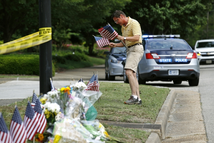 Rich Lindgren, of Virginia Beach, Va., places American flags at a makeshift memorial at the edge of a police cordon in front of a municipal building that was the scene of a shooting, Saturday, June 1, 2019, in Virginia Beach, Va. DeWayne Craddock, a longtime city employee, opened fire at the building Friday before police shot and killed him, authorities said. (AP Photo/Patrick Semansky)