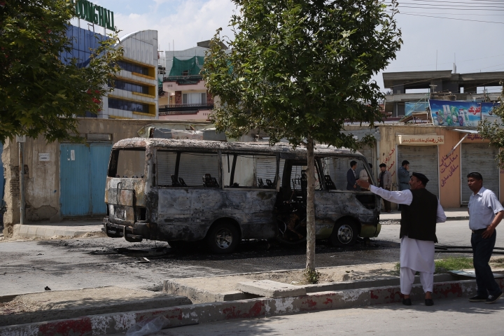 Security personnel inspect the site of a blast in Kabul, Afghanistan, Monday, June 3, 2019. Afghan officials say at least one person has been killed when a sticky bomb attacked into a bus detonated in the capital Kabul. Nasrat Rahimi, spokesman for the interior ministry confirms Monday's attack has targeted the bus carrying employees of the Independent Administrative Reform and civil service Commission. (AP Photo/Rahmat Gul)