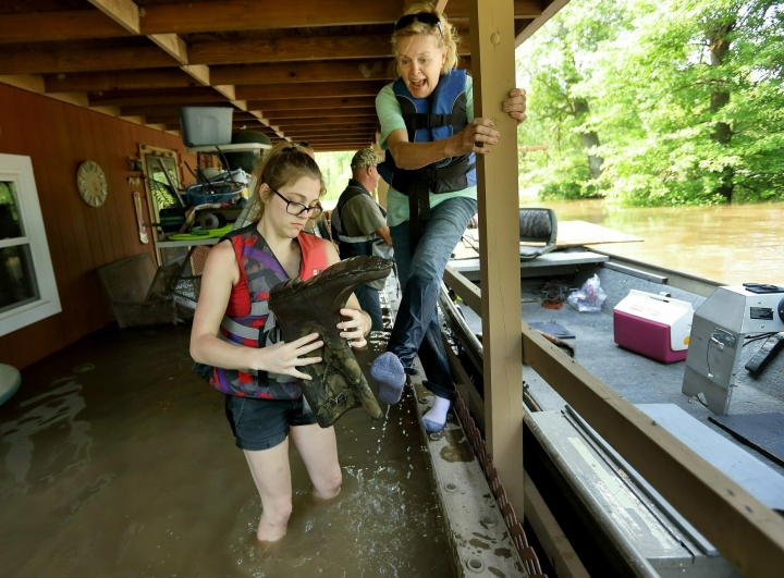 Emily Kientzel empties the water out of her grandmother Joan FitzGerald's boot that filled with floodwater from the Mississippi River, as they check on the home of a friend outside of Portage des Sioux, Mo., Sunday, June 2, 2019. The pair are standing on the second story balcony of the home that has more than a foot of water in it. (David Carson/St. Louis Post-Dispatch via AP)