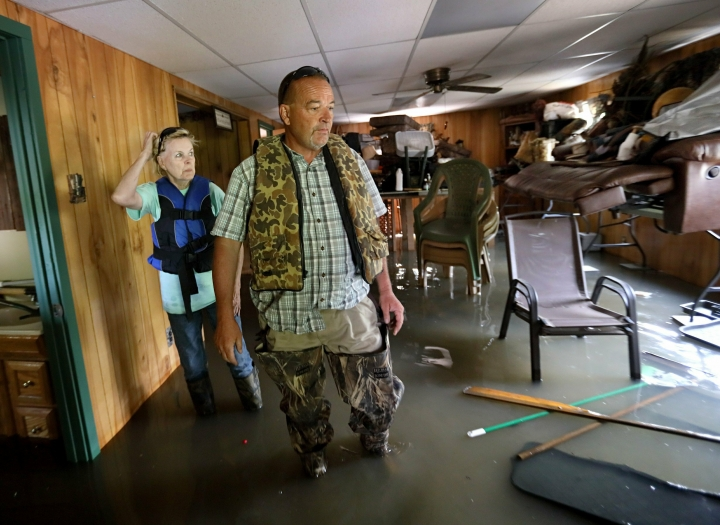"""Steve Schade looks over Mississippi River floodwater that fills the second floor of his home outside of Portage des Sioux, Mo., Sunday, June 2, 2019. Schade's home is on the banks of the Mississippi River and while the first floor of his """"clubhouse"""" had regularly flooded, this is the first time the second story of his home, where his living space is, has flooded since he bought the place in 2004. (David Carson/St. Louis Post-Dispatch via AP)"""
