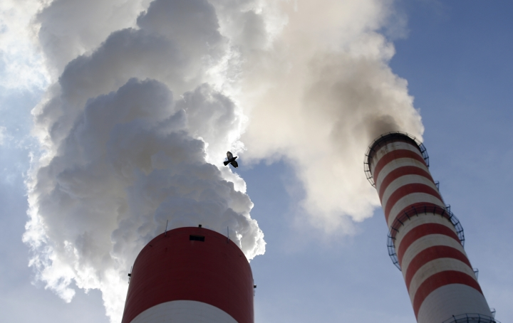 FILE - In this Wednesday, Oct. 3, 2018 file photo, a bird flies past as smoke emits from the chimneys of Serbia's main coal-fired power station near Kostolac, Serbia. People in all major cities across the Western Balkans face alarming levels of air pollution that are reducing resident's life expectancies, as the underdeveloped, politically fragile region is still heavily reliant on burning coal to generate electricity and heat, the U.N. Environment Program said in a new report on Monday June 3, 2019. (AP Photo/Darko Vojinovic, File)
