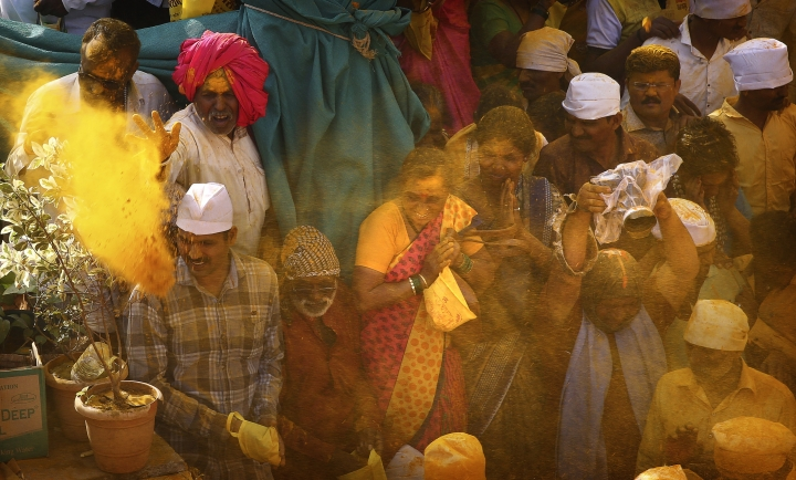 In this Monday, June 3, 2019, photo, devotees are smeared in the spice turmeric during the celebration of the Bhandara Festival, or the Festival of Turmeric, at the Jejuri temple in Pune district, Maharashtra state, India. During the festival, devotees use the golden powder to worship the deity Lord Khandoba, widely known as a descendant of the sun, and to celebrate his victory over the demons Mani and Malla. (AP Photo/Rafiq Maqbool)
