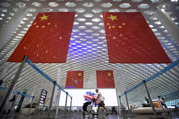 FILE - In this Oct. 10, 2018, file photo, a traveler pushes his luggage beneath large Chinese flags hanging from the ceiling in Shenzhen Bao'an International Airport in Shenzhen in southern China's Guangdong province. China has on Tuesday, June 4, 2019, issued a travel warning for the U.S., saying Chinese visitors have been interrogated, interviewed and subjected to other forms of what it called harassment by U.S. law enforcement agencies. (AP Photo/Mark Schiefelbein, File)