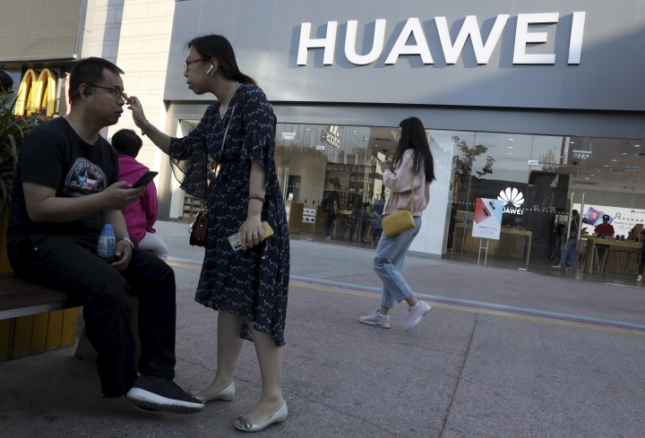 In this May 20, 2019, photo, a woman adjusts the glasses of a man outside a Huawei store in Beijing. The world's largest association of technology professionals has reversed a decision that would have excluded employees of Chinese tech giant Huawei and its affiliates from some editorial and peer review activities.(AP Photo/Ng Han Guan)