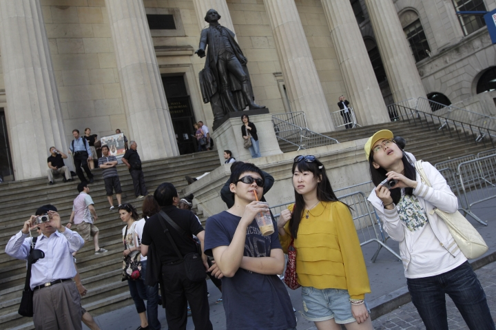 FILE - In this Friday, June 15, 2012, file photo, a group of tourists from China take in the sights of the New York Stock Exchange and Federal Hall National Memorial. Major hotel brands are bending over backward to cater to the needs of the world's most sought-after traveler: the Chinese tourist. China has issued a travel warning for the U.S. saying Chinese visitors have been interrogated, interviewed and subjected to other forms of what it called harassment by U.S. law enforcement agencies. (AP Photo/Mary Altaffer, File)