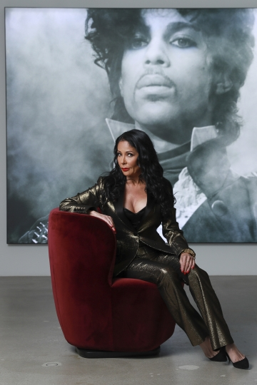 "Apollonia Kotero poses for a portrait in front of a photo of Prince at Warner Music Group in Los Angeles on Friday, May 31, 2019. Kotero, who recorded Prince's ""Sex Shooter,"" is one of several artists who spoke with The Associated Press about their experience working with the artist. The song is included on a posthumous album of Prince's music, ""Originals,"" due out this month. (Photo by Mark Von Holden/Invision/AP)"