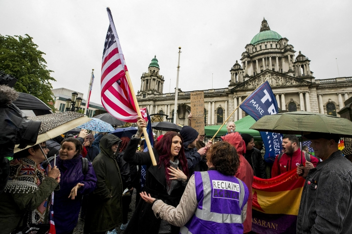 """Jayda Fransen former deputy leader of Britain First, centre holds a US flag, as she stages a corner protest with supporters at a """"Stop Trumpism"""" rally hosted by ExAct: Expat Action Group NI, at Belfast City Hall, in Belfast, Northern Ireland, Tuesday June 4, 2019. (Liam McBurney/PA via AP)"""