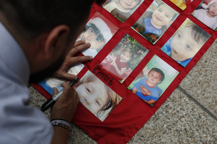 Abraham Fraijo labels a photograph with the name of his daughter Emilia, who he says was 3-years, three months, and 14 days old when she was killed along with 48 other children in a fire at the ABC daycare center, as family members mark the 10-year-anniversary of the tragedy in Mexico City, Wednesday, June 5, 2019. A handful of parents and relatives gathered to install bronze replicas of the children's shoes at a protest monument which stands in front of the government agency that oversaw the daycare. (AP Photo/Rebecca Blackwell)