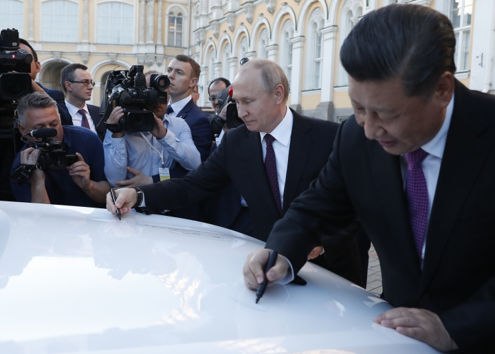 Russian President Vladimir Putin, second right, and Chinese President Xi Jinping, right, sign their names on a Havel F7 car during a presentation of the investment project on opening the Great Wall Motors' new Haval car factory in Russia's Tula Region in the Kremlin in Moscow, Russia, Wednesday, June 5, 2019. Putin hailed the launch of a Chinese car factory south of Moscow as a sign of burgeoning business ties. (Maxim Shipenkov/Pool Photo via AP)