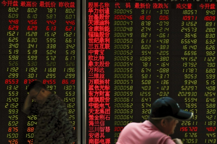 A man walks by an electronic board displaying stock prices at a brokerage house in Beijing Thursday, June 6, 2019. Asian stocks were mixed on Thursday as traders kept a close watch on impending U.S. tariffs on Mexico amid a standstill in its talks with China. (AP Photo/Andy Wong)