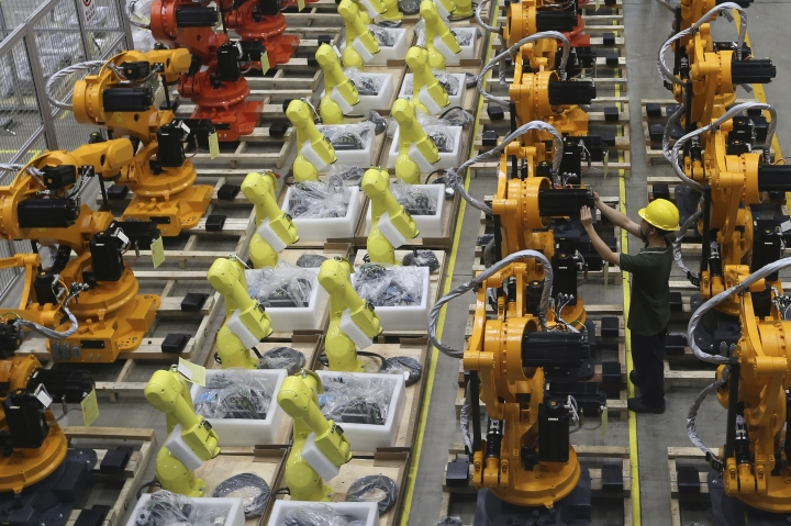 "A worker checks on robot arms at a factory in Nanjing in east China's Jiangsu province, Thursday, June 6, 2019. China's Commerce Ministry will release a list of ""unreliable"" foreign companies in the near future, a spokesman said Thursday, without giving a specific date. The new list, announced last week, is widely seen as a response to a U.S. decision to put Huawei Technologies on a blacklist for alleged theft of intellectual property and evasion of Iran sanctions. (Chinatopix via AP)"