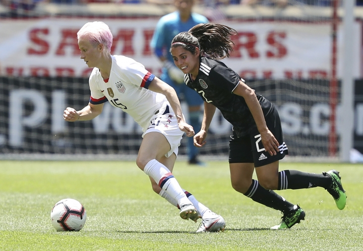 FILE- In this Sunday, May 26, 2019, file photo, United States forward Megan Rapinoe, left, dribbles the ball away from Mexico defender Kenti Robles during the first half of an international friendly soccer match in Harrison, N.J. The World Cup is not just about soccer for many of the players and teams in France. For the defending champion U.S. women's team, that means focus on the fight for equal pay to the men's national team.(AP Photo/Steve Luciano, File)