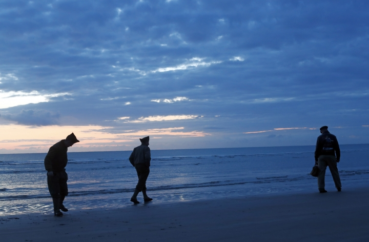 World War II reenactors walk along Omaha Beach, in Normandy, France, at dawn on Thursday, June 6, 2019 during commemorations of the 75th anniversary of D-Day. (AP Photo/Thibault Camus)