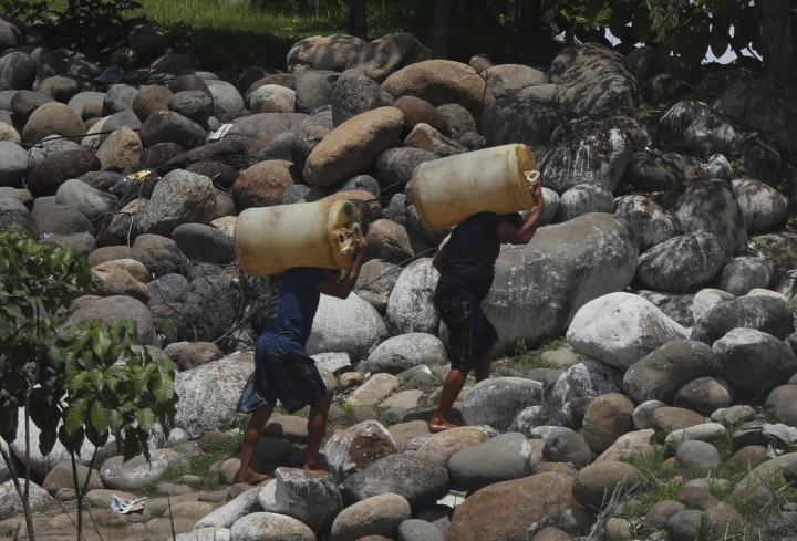 Men carry containers of black-market gasoline, recently brought illegally across the Suchiate River on rafts, near Ciudad Hidalgo, Mexico, Thursday, June 6, 2019. U.S. President Donald Trump has pledged to impose 5% tariffs on Mexican products unless Mexico country prevents Central American migrants from traveling through its territory. Some migrants pay raft operators in order to avoid swimming or going through the official border crossing. (AP Photo/Marco Ugarte)