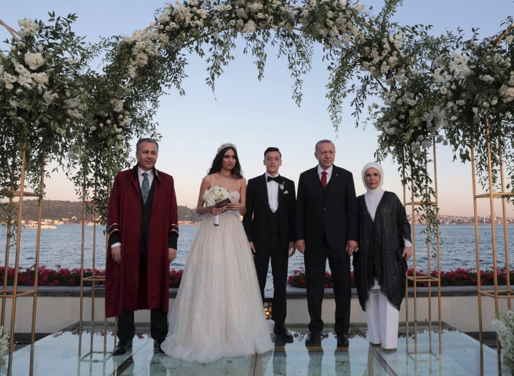 Turkey's President Recep Tayyip Erdogan, second right, Turkish-German soccer player Mesut Ozil, center, his wife Amine Gulse, second left, Erdogan's wife Emine Erdogan and Istanbul Governor and temporary mayor Ali Yerlikaya pose for a photo during a wedding ceremony over the Bosporus in Istanbul, Friday, June 7, 2019.(Presidential Press Service via AP, Pool)