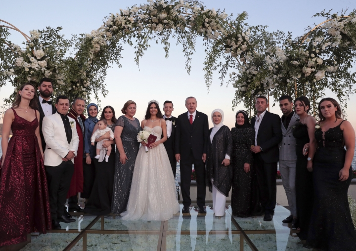 Turkey's President Recep Tayyip Erdogan, center right, Turkish-German soccer player Mesut Ozil, centre, his wife Amine Gulse, center left, Erdogan's wife Emine Erdogan pose for a photo with family members of newly wed couple during a wedding ceremony over the Bosporus in Istanbul, Friday, June 7, 2019.(Presidential Press Service via AP, Pool)