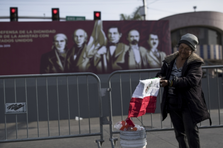 "A woman unfurls a Mexican flag in front of the stage where Mexican President Andres Manuel Lopez Obrador will hold a rally, in Tijuana, Mexico, Saturday, June 8, 2019. Mexican President Andres Manuel Lopez Obrador is to hold a rally in Tijuana even as President Trump has put on hold his plan to begin imposing tariffs on Mexico on Monday, saying the U.S. ally will take ""strong measures"" to reduce the flow of Central American migrants into the United States. (AP Photo/ Hans-Maximo Musielik)"