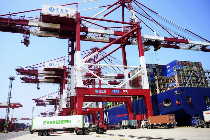 Trucks move shipping containers at a port in Qingdao in eastern China's Shandong province, Monday, June 10, 2019. China has reported a sharp jump in its trade surplus for May, as imports fell off and exports edged up. (Chinatopix via AP)