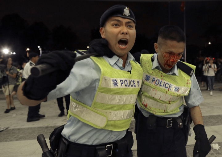 A Hong Kong police officer with blood flowing down his face is assisted by his colleague after clashing with protesters in a rally against the proposed amendments to the extradition law at the Legislative Council in Hong Kong during the early hours of Monday, June 10, 2019. The extradition law has aroused concerns that this legislation would undermine the city's independent judicial system as it allows Hong Kong to hand over fugitives to the jurisdictions that the city doesn't currently have an extradition agreement with, including mainland China, where a fair trial might not be guaranteed. (AP Photo/Vincent Yu)