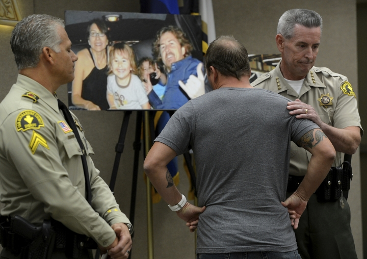"""FILE - In this Nov. 7, 2014, file photo, Michael McStay is consoled by San Bernardino County Sheriff John McMahon as he reacts before talking to the media about his late brother's family at a news conference in San Bernardino, Calif. A jury verdict will be read in the case of a Southern California man charged with killing a family of four and burying their bodies in the desert. The verdict will be read Monday, June 10, 2019, in court in San Bernardino in the quadruple murder case against 62-year-old Charles """"Chase"""" Merritt. (Jennifer Cappuccio Maher/The Orange County Register via AP, File)"""