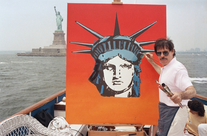 CORRECTS MARY MAX'S AGE TO 52, NOT 53 - FILE - In this July 4, 1987, file photo, artist Peter Max works on a painting of the Statue of Liberty aboard a boat in New York Harbor, as part of the Fourth of July festivities New York. Authorities say Mary Max, 52, the wife of the artist Peter Max, was found dead Sunday, June 9, 2019, in New York, of a suspected suicide amid a family fight over her husband's work. Her death comes two weeks after The New York Times published a story detailing legal battles over the work of Peter Max, a prolific creator of colorful, psychedelic art who is now living with dementia at age 81. (AP Photo/David Bookstaver, File)