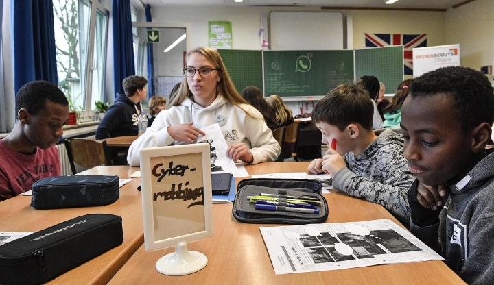 Senior student and media scout Joeline Klaar teaches young pupils behind a sign reading 'Cyber Mobbing' during a lesson in social media and internet at a comprehensive school in Essen, Germany, Monday, March 18, 2019. According to experts and teachers the peer projects in which teenagers teach their younger schoolmates how to stay safe and sane online have proven to be especially successful.(AP Photo/Martin Meissner)