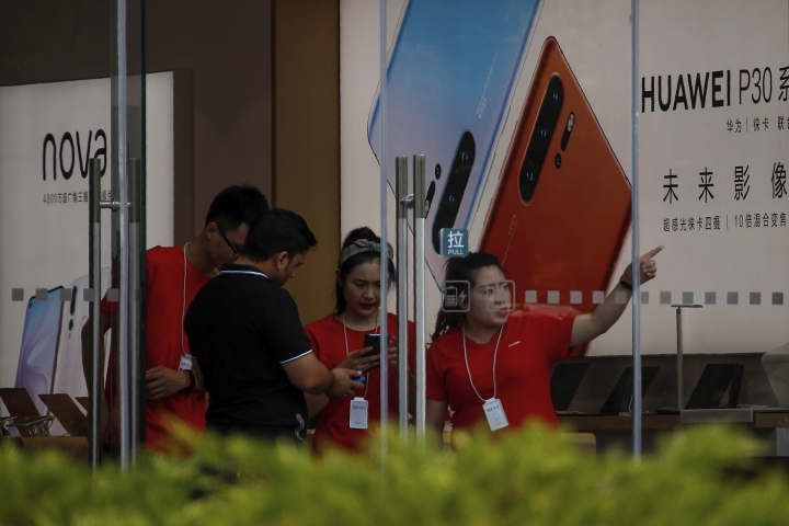 "Staffers help a tourist search for directions at a Huawei retail store in Beijing, Tuesday, June 11, 2019. Chinese tech giant Huawei said Tuesday it would have become the world's number one smartphone maker by year's end if it were not for ""unexpected"" circumstances — a hint that pressure from the U.S. may be hurting its sales. (AP Photo/Andy Wong)"