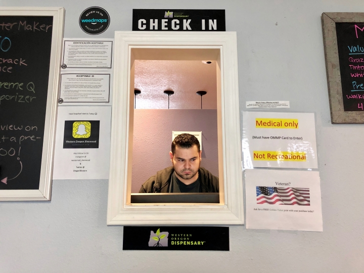 In this April 8, 2019, photo, Roberto Gonzalez, the general manager of Western Oregon Dispensary in Sherwood, Ore., waits for customers. The dispensary is one of two medical-only marijuana dispensaries left in Oregon. An Associated Press analysis has found existing medical marijuana programs take a hit when states legalize cannabis for all adults. (AP Photo/Gillian Flaccus)