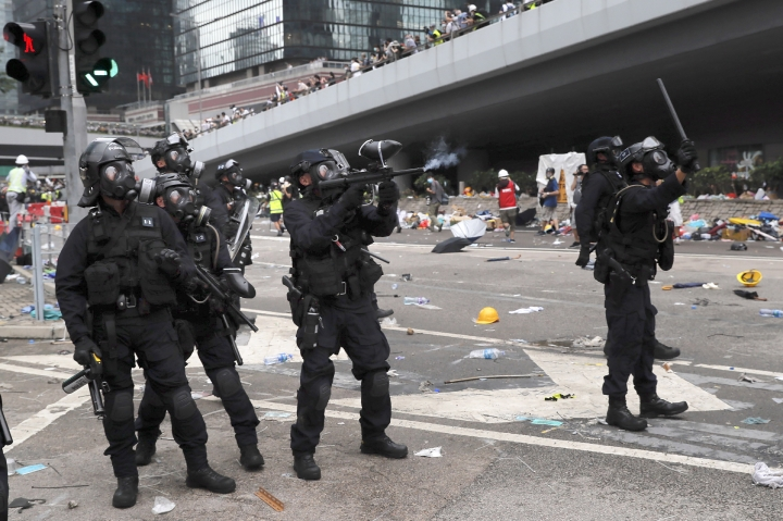 A policeman fires what a crowd control weapon towards protesters near the Legislative Council in Hong Kong, Wednesday, June 12, 2019. Hong Kong police have used tear gas and high-pressure hoses against thousands of protesters opposing a highly controversial extradition bill outside government headquarters. (AP Photo/Kin Cheung)