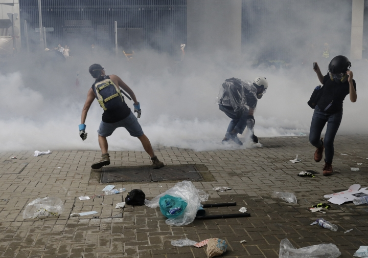 Protesters throw tear gas back at riot police outside the Legislative Council in Hong Kong, Wednesday, June 12, 2019. Hong Kong police have used tear gas and high-pressure hoses against thousands of protesters opposing a highly controversial extradition bill outside government headquarters. (AP Photo/Vincent Yu)