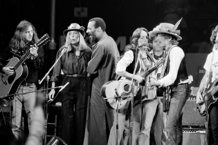 """FILE - In this Dec.1975 file photo, musicians Roger McGuinn, Joni Mitchell, Richi Havens, Joan Baez and Bob Dylan perform the finale of the The Rolling Thunder Revue, a tour headed by Dylan. Martin Scorsese's latest film, """"Rolling Thunder Revue: A Bob Dylan Story By Martin Scorsese,"""" is a blistering semi-fictional documentary that resurrects Dylan's mythic 1975-1976 tour and its rambling cavalcade across a post-Vietnam America. The film, which opens Wednesday in limited theaters and on Netflix, includes restored performance footage, scenes of the backstage circus and interviews with many of the participants, including Dylan's first on-camera interview in 10 years. (AP Photo, File)"""