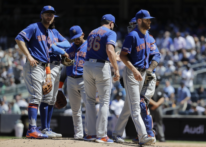 New York Mets manager Mickey Callaway, center, takes starting pitcher Zack Wheeler, right, out of the game during the fifth inning against the New York Yankees in the first baseball game of a doubleheader, Tuesday, June 11, 2019, in New York. (AP Photo/Frank Franklin II)