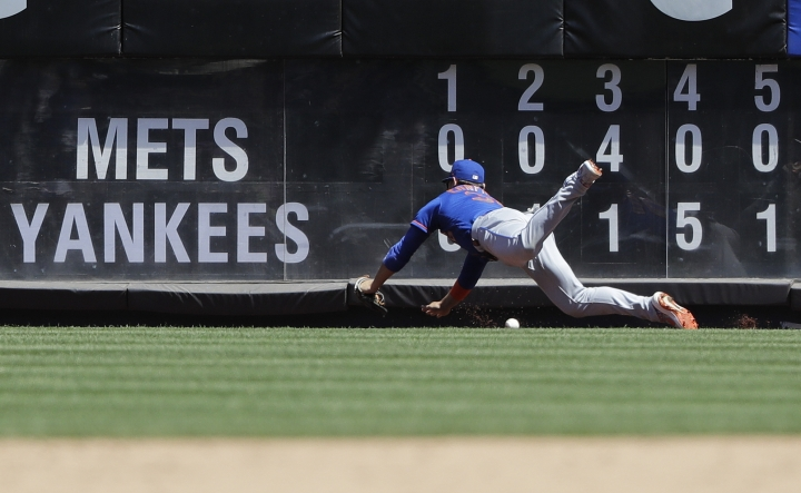 New York Mets right fielder Michael Conforto misjudges a ball hit by New York Yankees' Brett Gardner for an RBI triple during the fifth inning in the first game of a baseball doubleheader Tuesday, June 11, 2019, in New York. (AP Photo/Frank Franklin II)