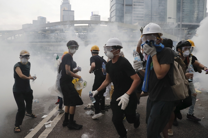 Demonstrators react to a cloud of tear gas near the Legislative Council in Hong Kong, Wednesday, June 12, 2019. Hong Kong police fired tear gas and high-pressure water hoses against protesters who had massed outside government headquarters Wednesday in opposition to a proposed extradition bill that has become a lightning rod for concerns over greater Chinese control and erosion of civil liberties in the semiautonomous territory. (AP Photo/Kin Cheung)