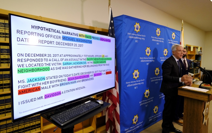 """With a hypothetical police report displayed, San Francisco District Attorney George Gascon talks about the implementation of an artificial intelligence tool to remove potential for bias in charging decisions during a news conference Wednesday, June 12, 2019, in San Francisco. In a first-of-its kind experiment, San Francisco prosecutors are turning to artificial intelligence to reduce bias in the criminal courts. They are adopting a system that strips certain identifying details from police reports and leaves only key facts to govern charging decisions. Gascon announced his office will begin using the technology in July to """"take race out of the equation"""" when deciding whether to accuse suspects of a crime. (AP Photo/Eric Risberg)"""