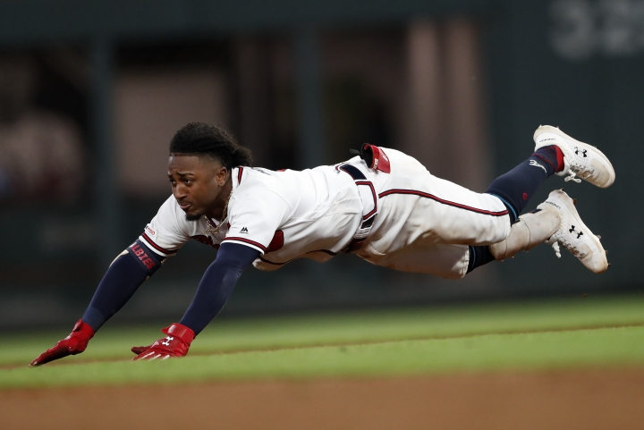 Atlanta Braves' Ozzie Albies dives into second base with a double during the fifth inning of the team's baseball game against the Pittsburgh Pirates on Wednesday, June 12, 2019, in Atlanta. (AP Photo/John Bazemore)