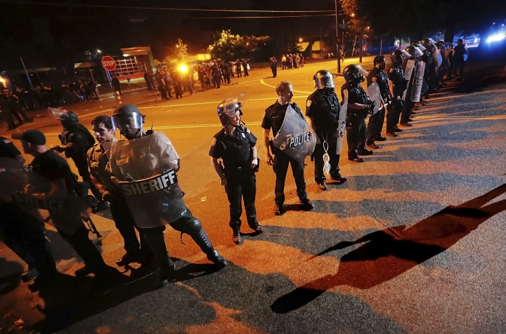 Authorities maintain a perimeter around the crime scene after protesters took to the streets of the Frayser community in anger against the shooting a youth by U.S. Marshals earlier in the evening, Wednesday, June 12, 2019, in Memphis, Tenn. Dozens of protesters clashed with authorities, throwing stones and tree limbs until law enforcement personnel broke up the angry crowd with tear gas. (Jim Weber/Daily Memphian via AP)