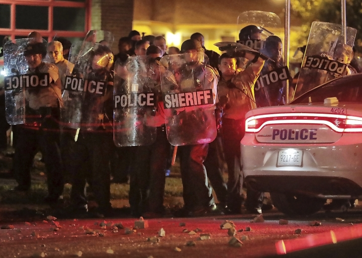 Shelby County Sheriff's deputies brace against the crowd as protesters take to the streets of the Frayser community in anger against the shooting a youth identified by family members as Brandon Webber by U.S. Marshals earlier in the evening, Wednesday, June 12, 2019, in Memphis, Tenn. (Jim Weber/Daily Memphian via AP)