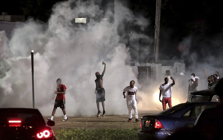 Frayser community residents taunt authorities as protesters take to the streets in anger against the shooting of a youth identified by family members as Brandon Webber by U.S. Marshals earlier in the evening, Wednesday, June 12, 2019, in Memphis, Tenn. Dozens of angry protesters clashed with police throwing stones and tree limbs until police forces broke the mob up with tear gas. (Jim Weber/Daily Memphian via AP)