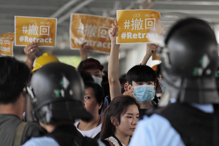 """Riot police surround protesters near the Legislative Council in Hong Kong, Thursday, June 13, 2019. After days of silence, Chinese state media is characterizing the largely peaceful demonstrations in Hong Kong as a """"riot"""" and accusing protesters of """"violent acts."""" (AP Photo/Kin Cheung)"""